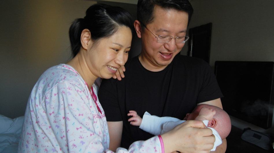 "New parents Wu Lili (left) and Mo Shiwei hold their 29-day-old baby boy. The new mom is staying at the Weige center in Beijing, which provides luxury accommodation  and 24-hour nursing staff to woman who are participating in the Chinese tradition of ""sitting the month."" (NPR)"