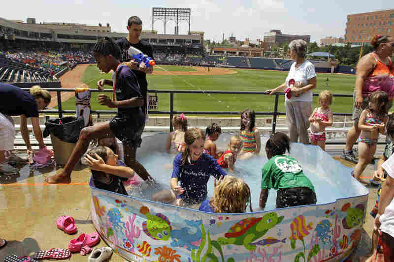 Children keep cool in a swimming pool in right field at Canal Park in Akron, Ohio, on Wednesday.