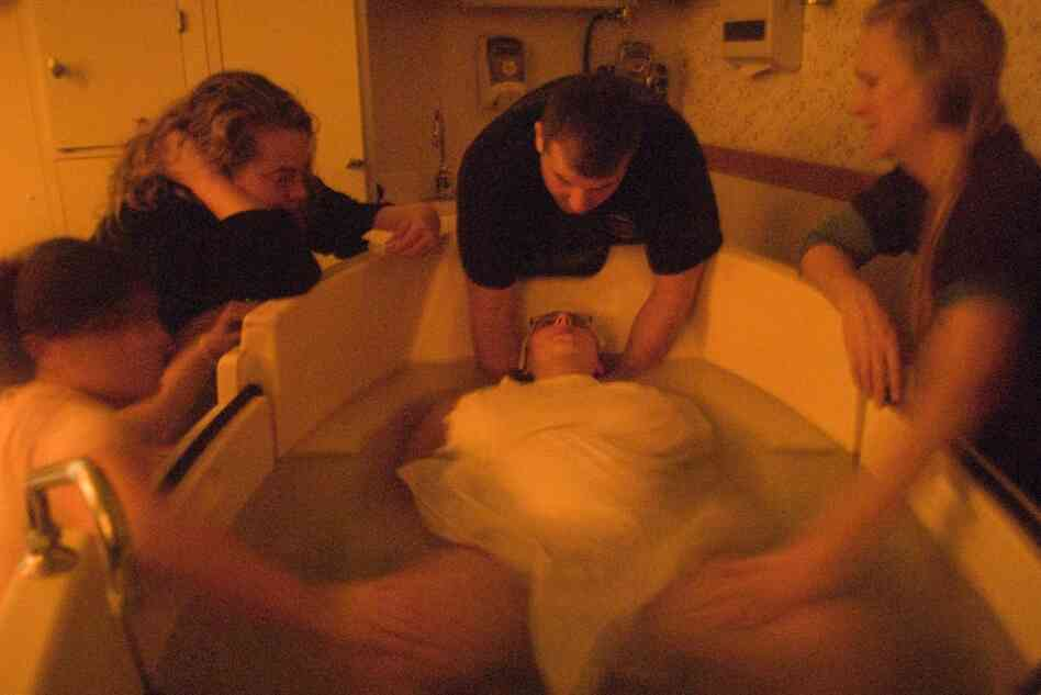 Meg Tudryn labors in a birthing tub, surrounded by friends Kate Roche-Szoc (from left) and Dawn Oldford, husband T.J. Tudryn, and doula Beth Fairservis. Tudryn is delivering at The Birthplace, located at Baystate Franklin Medical Center in Greenfield, Mass., where she is also a nurse.