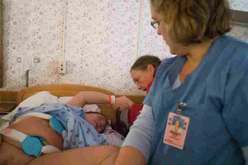 Nurse Wendy Swasey watches while Tudryn pushes with the support of her mother, Lori Baronas.