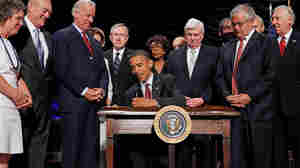 President Obama signs the financial reform bill into law, July 21, 2010. Vice President Joe Biden, Senate Majority Leader Harry Reid (D-NV), then Senate Banking Chairman Christopher Dodd (D-CT), House Financial Services Committee Chairman Barney Frank (D-MA) and other lawmakers look on.