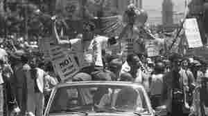 San Francisco Supervisor Harvey Milk is seen in the city's 7th annual gay freedom parade in 1978. Milk was the first openly gay man to be elected to public office in California. Earlier this month, the state became the first in the nation to mandate teaching of gay history in social studies classes.