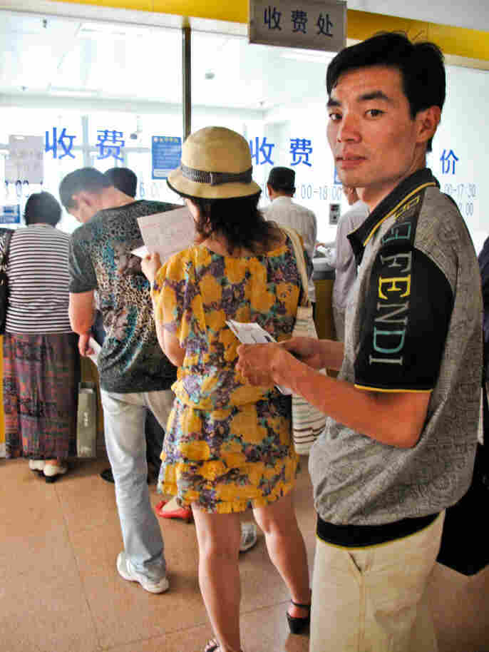 Queuer Li Qicai waits in line at a  Shanghai hospital to collect traditional Chinese  medicine for a customer. He says he does a dozen hospital jobs a  week.