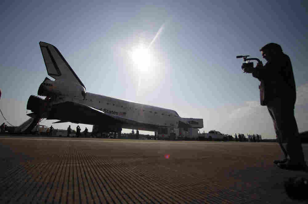 A videographer records post-landing activities as space shuttle Atlantis is readied to be towed at the Kennedy Space Center.