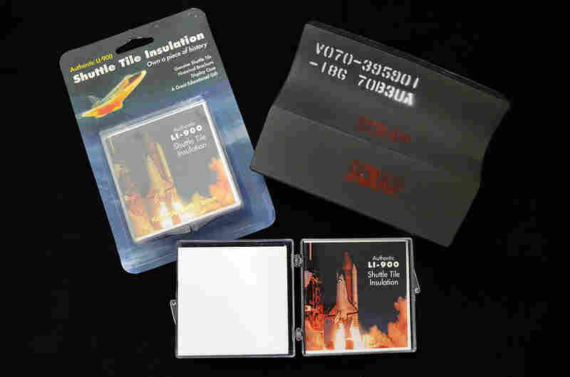 Examples of commercial reproductions of space shuttle heat shield tiles alongside a real tile (top right) that was never used. Parts of the space shuttle, or replicas thereof, attract space memorabilia collectors for their rarity and authenticity.