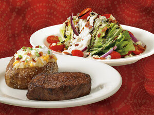 There, behind the sirloin steak and baked potato, is Outback Steakhouse's calorie-rich blue cheese wedge salad.