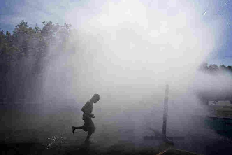 Jayson Hamler runs under a spray of water outside a school on Wednesday in Milwaukee.