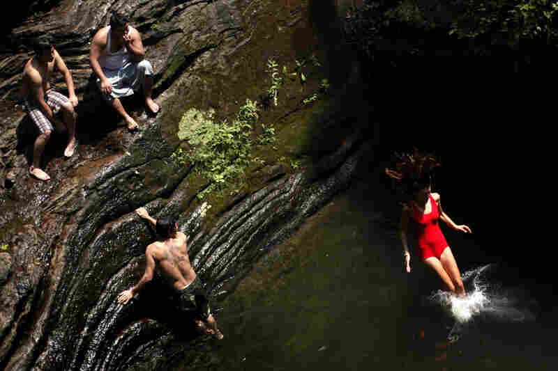 Bathers beat the midday heat at the Devil's Pool in Wissahickon Valley Park on Wednesday in Philadelphia.