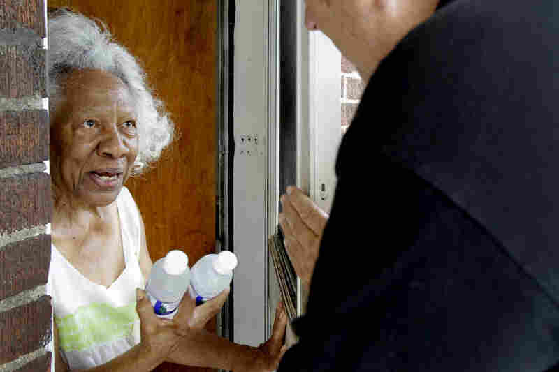 Lillie Walker, 90, accepts bottles of cold water on Monday in Jennings, Mo.