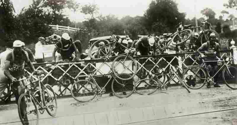 Impatient cyclists climb over the railroad crossing barrier during the 1932 race. That year the tour was shortened by about 357 miles compared to the previous year.