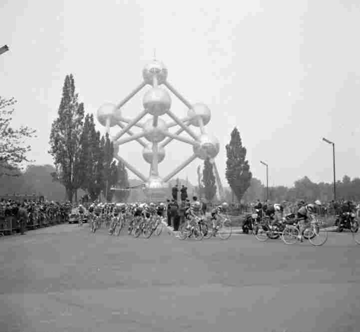 Racing cyclists pass the Atomium, a monument in Brussels, 1960.