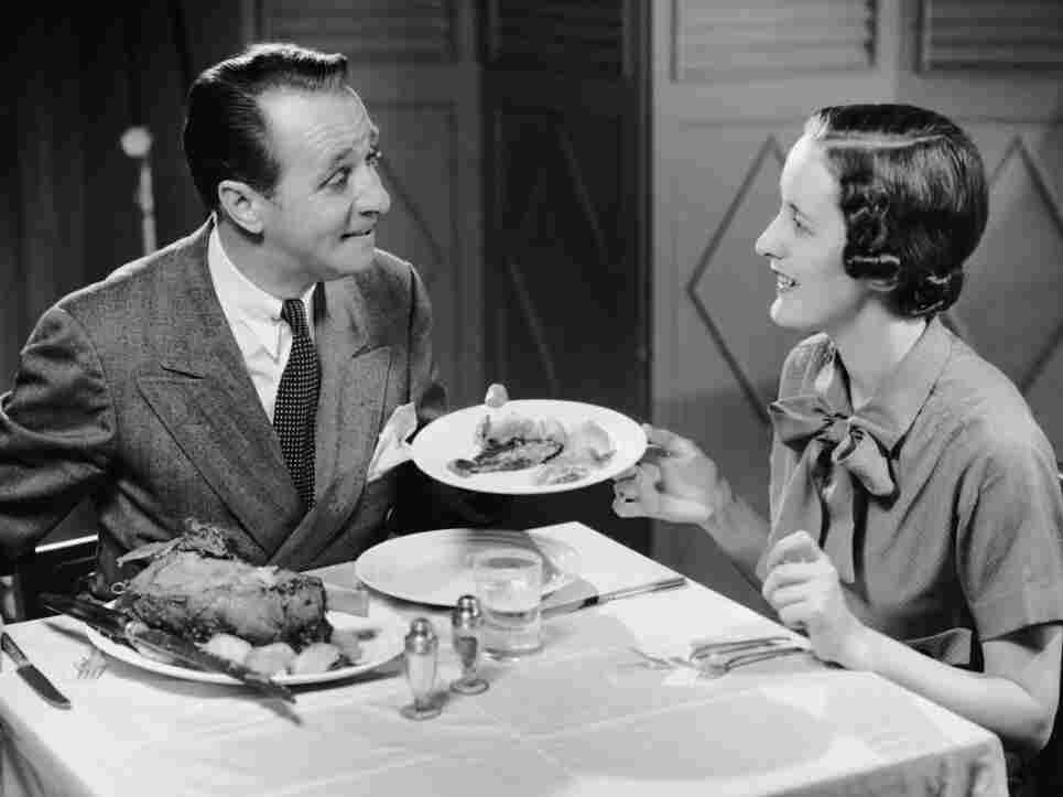 CIRCA 1950s:  Husband serving wife dinner.