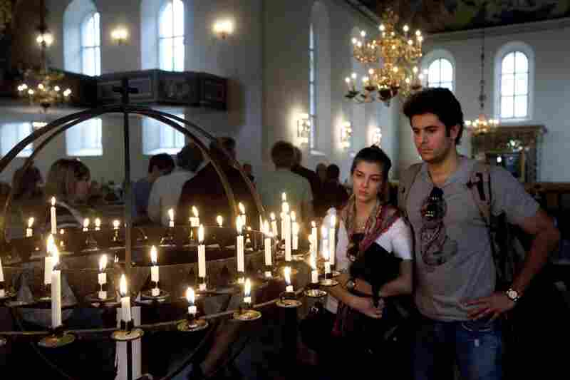 People light candles in Oslo Cathedral on Saturday to pay tribute to the victims of the attacks.