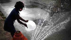 Jazia Pratt fills a bucket with water from a fire hydrant in the afternoon summer heat in Philadelphia.