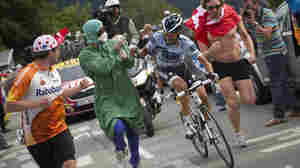 Defending Tour de France winner Alberto Contador is harangued by a man dressed in medical togs, during Contador's climb of the Alpe d'Huez.