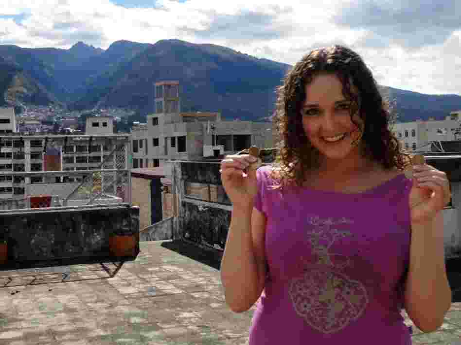Teacher Rebecca Kayes shows off the dollar coins she uses in Quito, Ecuador.