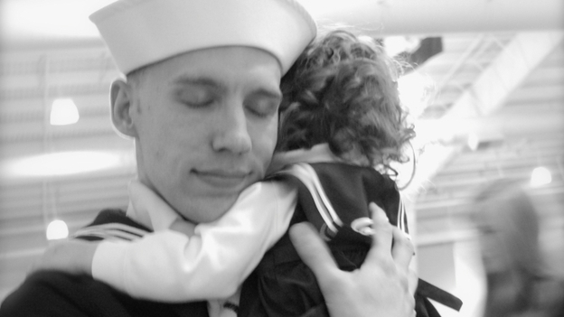 Justin Bock holds his daughter, Lina, at his graduation from basic training earlier this year. Bock decided to enlist in the Navy after both he and his wife, Ashley, were laid off. (Courtesy of the Bocks)
