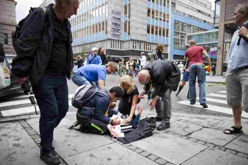 People tend to a wounded person after the explosion.