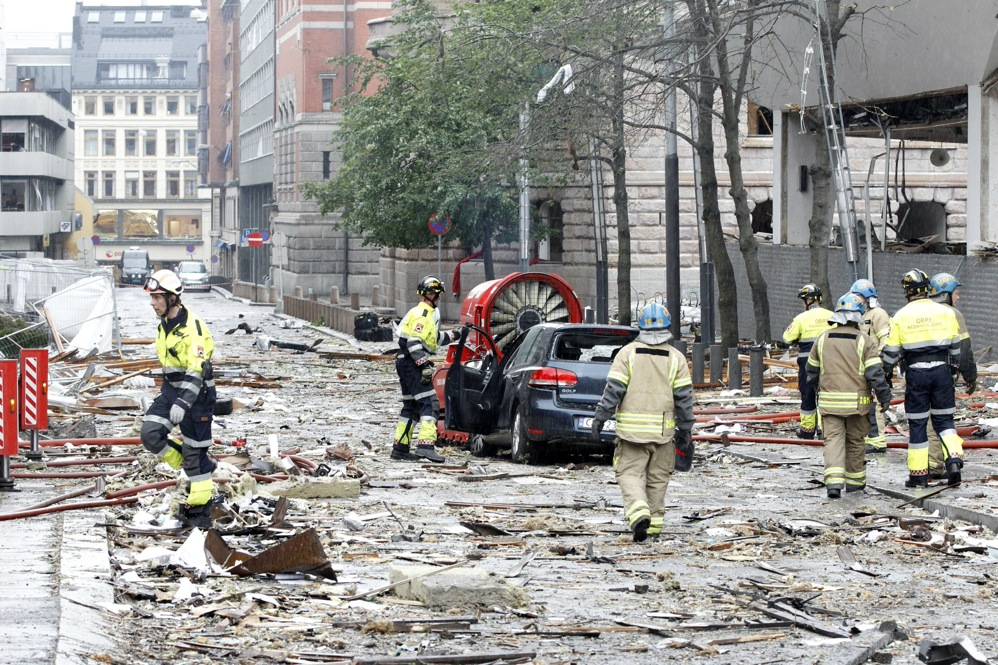 Firefighters work the scene of a debris-filled street near the site of the blast.