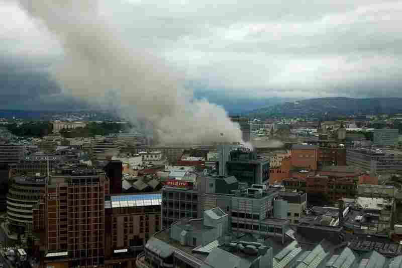 Smoke rises from the city center following the explosion.