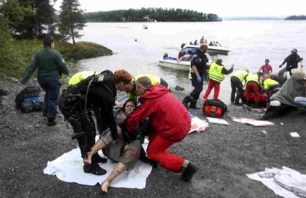 A wounded woman is brought ashore from Norway's Utoya Island after being rescued from a gunman who went on a killing rampage at a summer youth camp southwest of Oslo Friday.