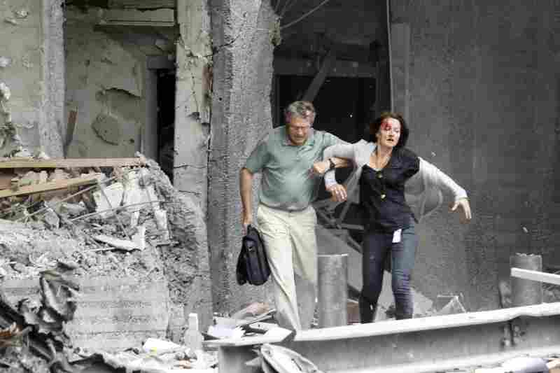 A man helps a wounded woman evacuate a building.