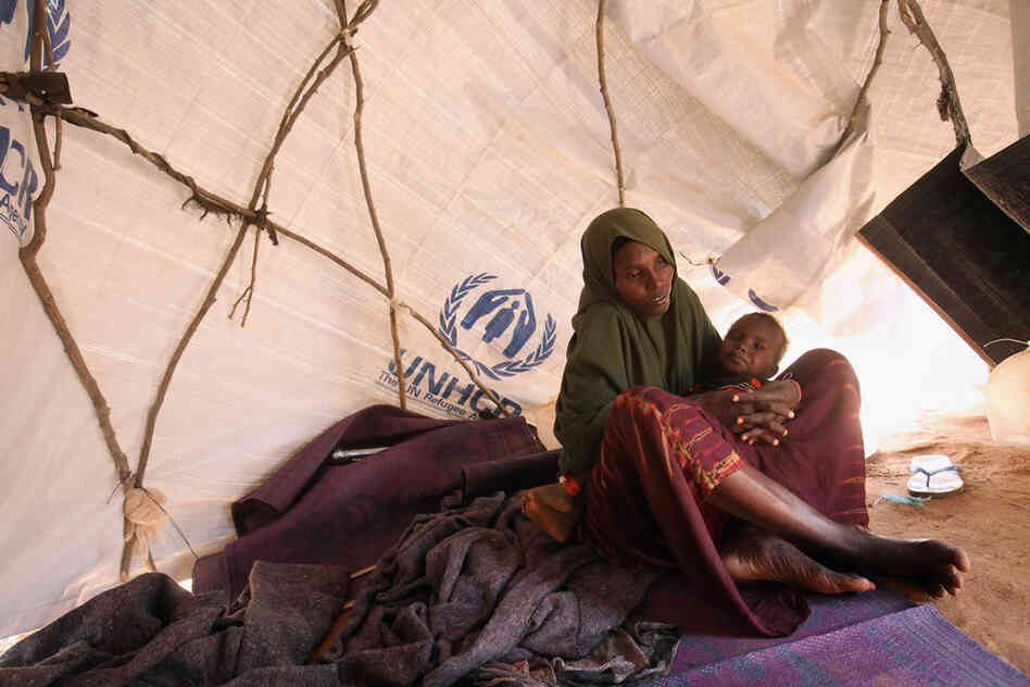 A Somali refugee mother and child sit in their makeshift hut on the edge of the Hagadera refugee camp on July 24. The camp makes up part of the giant Dadaab refugee