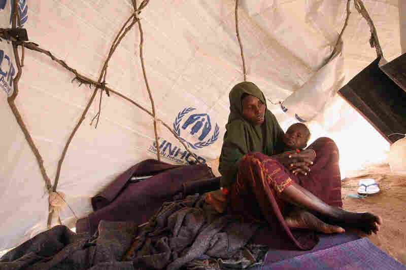 A Somali refugee mother and child sit in their makeshift hut on the edge of the Hagadera refugee camp on July 24. The camp makes up part of the giant Dadaab refugee settlement.