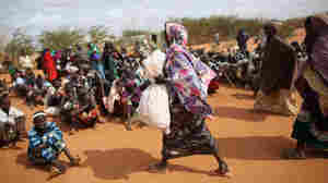 A Somali refugee woman carries a bag of food aid at the entrance to the registration area of the Dadaab refugee settlement in Kenya. While refugees receive international humanitarian aid, local Kenyans fighting drought get sacks of rice, beans and oil from the government.