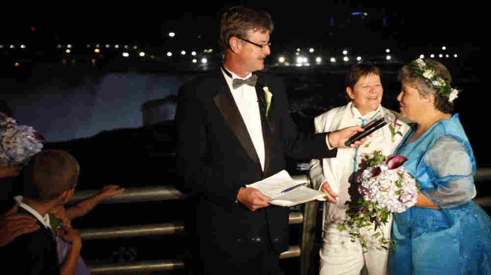 Kitty Lambert (right) and Cheryle Rudd are married by Niagara Falls Mayor Paul Dyster in Niagara Falls, N.Y., on Saturday. With a rainbow-lit Niagara Falls as a backdrop early Sunday, Lambert, 54, and Rudd, 53, were among the first gay couples to tie the knot with the blessing of the state, which last month became the sixth and largest to sanction gay marriage.