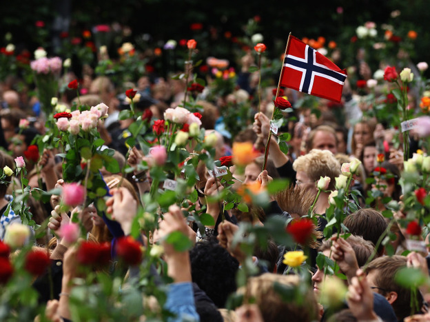 A Norwegian flag is held aloft Monday as people gather in Oslo's town center for a vigil following Friday's twin attacks in Oslo.