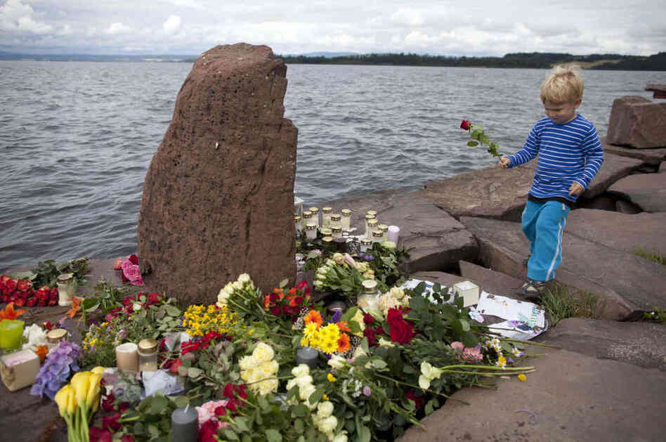 A child walks to place a rose amongst tributes in memory of those killed in the shooting massacre on Utoya island.
