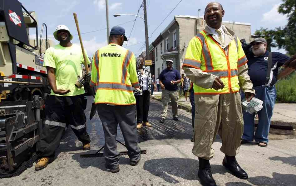 Philadelphia Mayor Michael Nutter (right) joins workers to draw attention to the city's streets repaving project July 18.