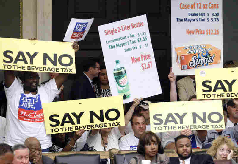 Opponents of a proposal to tax soda and other sugary drinks display signs at a City Council hearing in City Hall in June in Philadelphia. Mayor Michael Nutter has proposed the 2-cents-per-ounce tax on soda to generate money for the schools this year and help prevent deep cuts. Opponents, however, say it would cost hundreds of industry jobs.