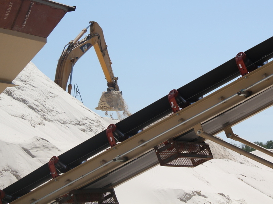 At the top of the bluffs, this backhoe shovels the sand that's been crushed and washed onto a conveyor belt that runs the sand through a drier before it's loaded into a rail car. (Kathleen Masterson for NPR)