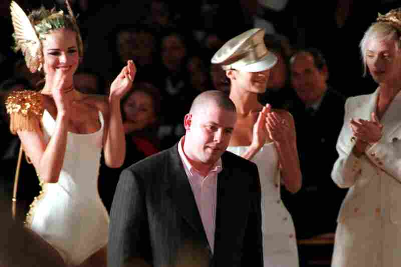 British fashion designer Alexander McQueen is surrounded by applauding models after a Paris show in 1997. The influential designer was found dead Thursday in his London home. He was 40 years old.