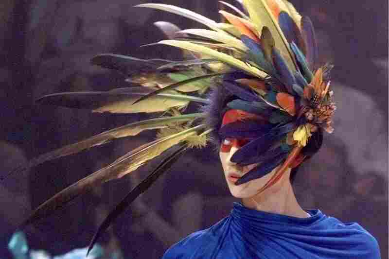 A model wears a feather headdress design by Alexander McQueen at a 1998 show in Paris. McQueen began his career at the age of 16 with an apprenticeship as a tailor on London's Savile Row.