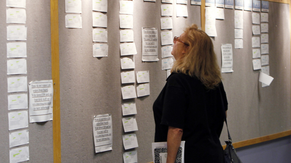 Lori Kamlet looks at posted job opportunities at a Denver employment office last Friday.