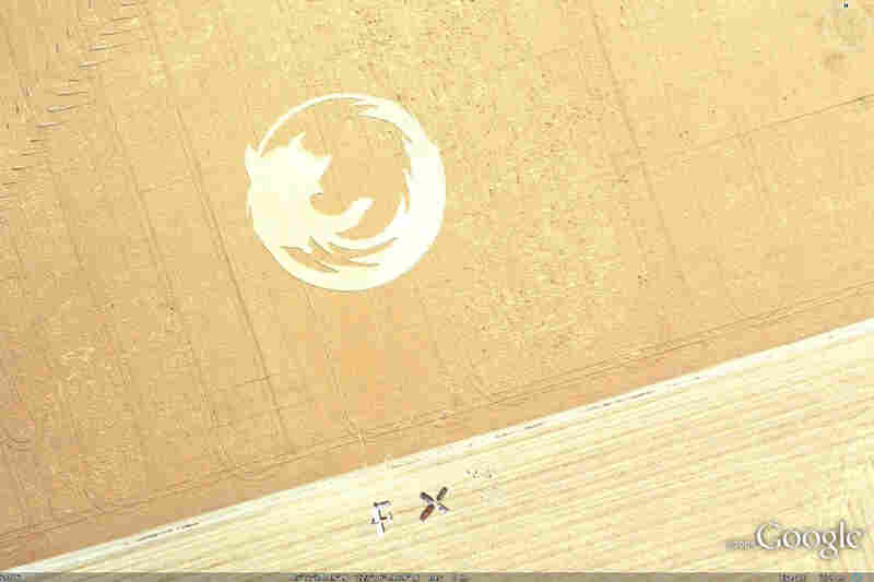 """This 220-foot-wide icon was created by the Oregon State University Linux Users Group to celebrate the launch of Firefox version 2. According to their website, it took a team of 12 people to stomp down the oats overnight. Just south of the logo you can see that they've also arranged their vehicles and bodies to spell out """"FX2."""""""