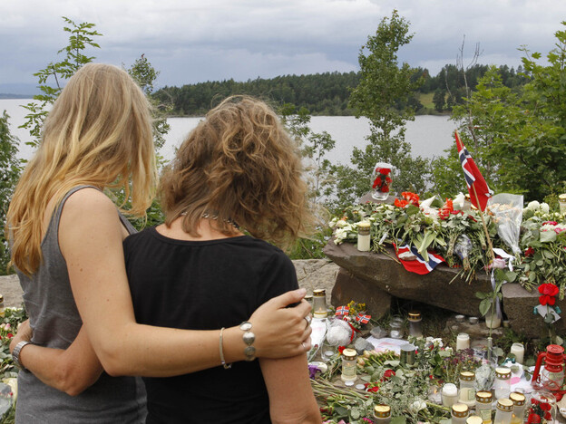 Two young women stood in silence Tuesday after placing flowers at a site off Norway's Utoya island, where a gunman killed at least 68 people.