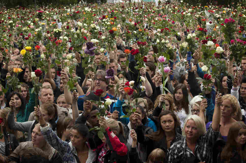 """People gather outside Oslo City Hall to participate in a """"rose march"""" in memory of the victims of Friday's bomb attack and shooting massacre."""