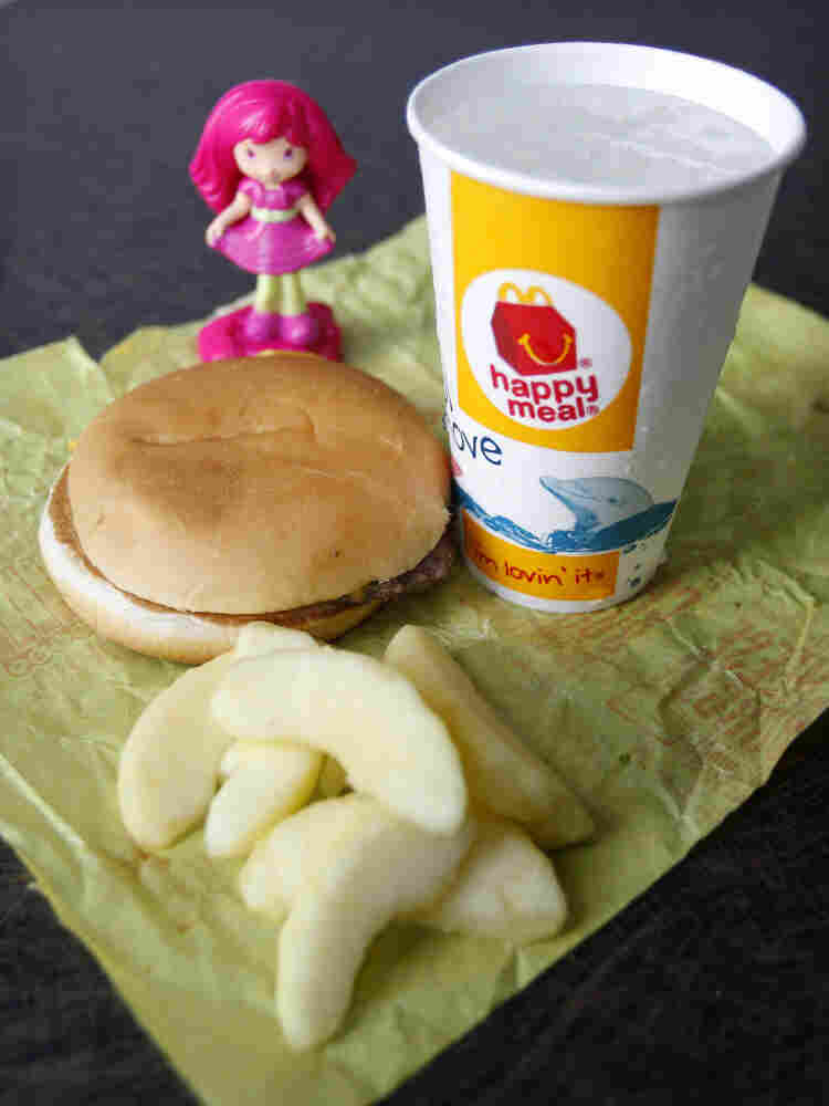 A McDonald's Cheeseburger Happy Meal with the new apple slices option is shown Tuesday. McDonald's Corp. says it is adding apple slices to every Happy Meal, part of the chain's larger push to paint itself as a healthy place to eat.