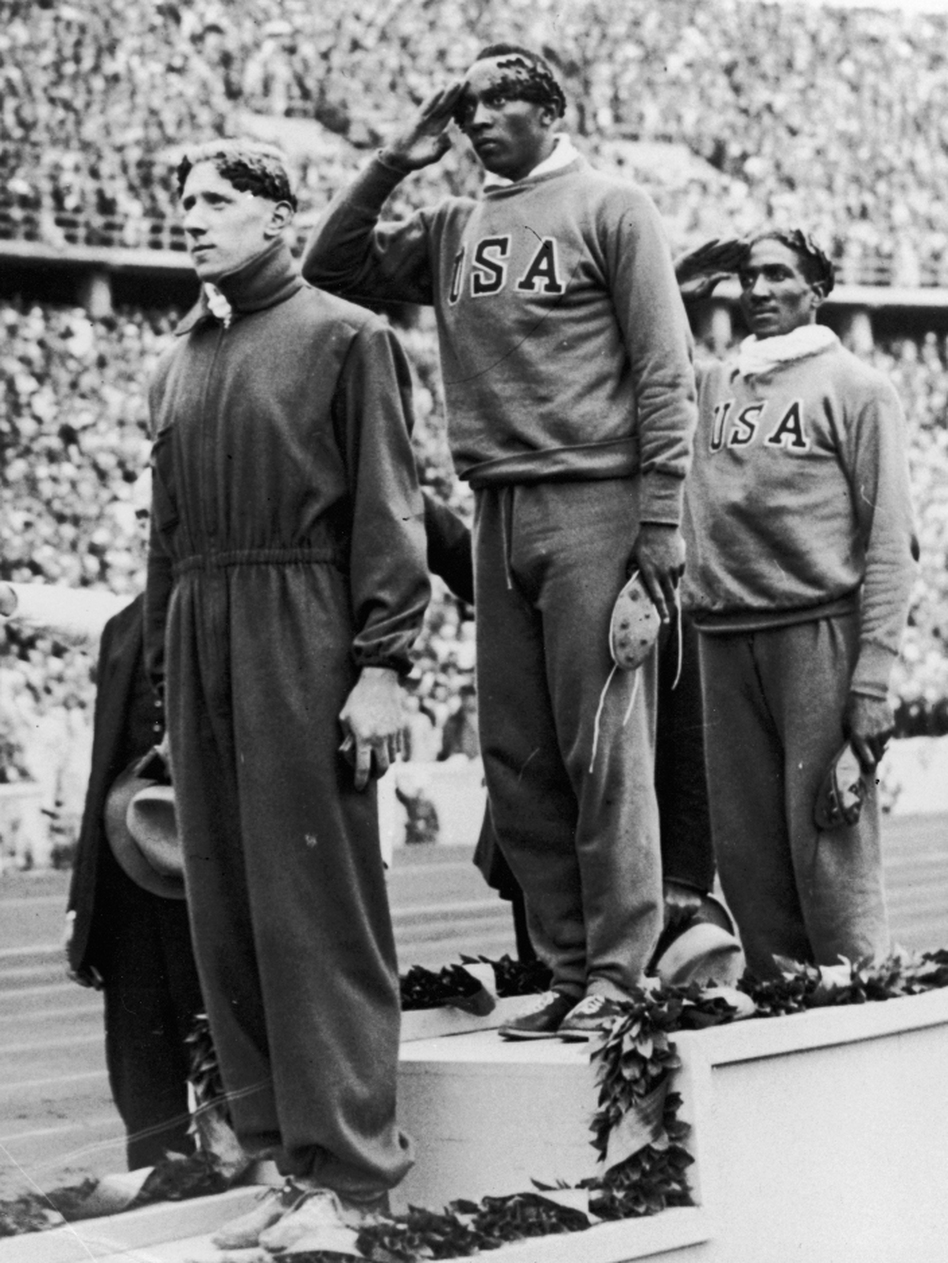 Jesse Owens stands on the podium after winning the gold medal in the 100-meter sprint at the 1936 Berlin Olympic Games. With him are bronze medalist Martinus Osendarp of Holland and silver medalist Ralph Metcalf, also of the U.S.