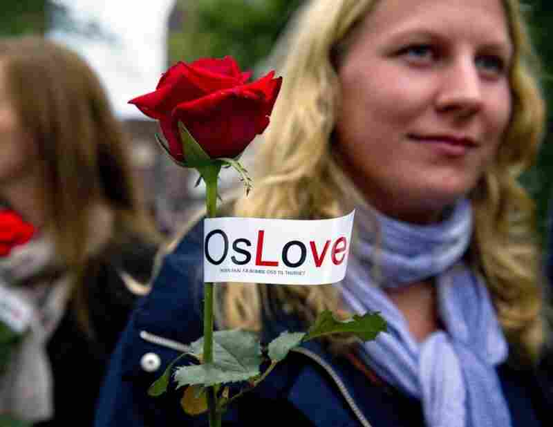 """Two women carry roses tagged with the slogan """"OsLove"""" as they joined as many as 150,000 people gathered for a flower vigil in Oslo."""