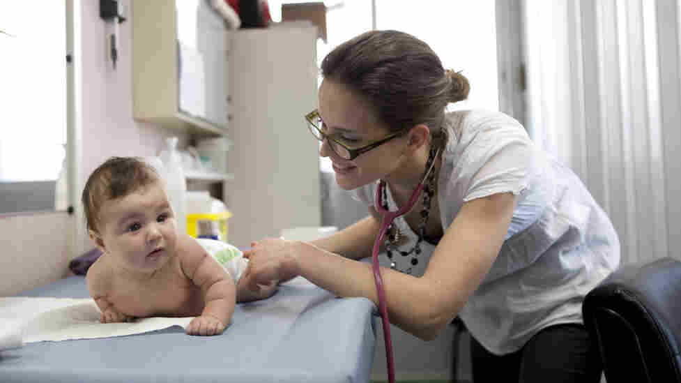 Dr. Sandrine Courtial examines 3.5-month-old Ayline Alhas at the Centre de Protection Maternelle et Infantile (PMI) in Savigny-sur-Orge, France, before giving her a vaccination. Ayline's mother, Melissa, has been bringing her in for free well-child check-ups since her birth.