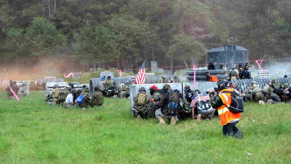 """Members of the Allied team take cover on the """"beach"""" — the field that faces the tree line where the Axis team has embedded.  Thousands of people traveled to a field in Jim Thorpe, Pa., to re-enact one of the most famous battles in history using paintball guns instead of real ammo."""