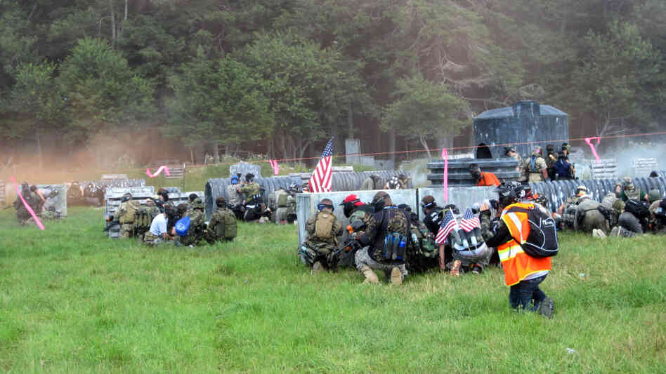 "Members of the Allied team take cover on the ""beach"" — the field that faces the tree line where the Axis team has embedded.  Thousands of people traveled to a field in Jim Thorpe, Pa., to re-enact one of the most famous battles in history using paintball guns instead of real ammo."