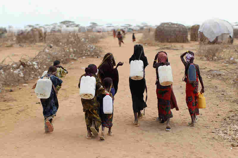 Somali refugees return from collecting water July 22 at the edge of the Dagahaley refugee camp, also part of the Dadaab settlement.