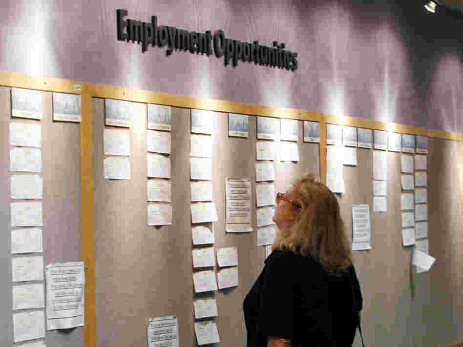 A woman looks at posted job opportunities at a Denver employment office last Friday.