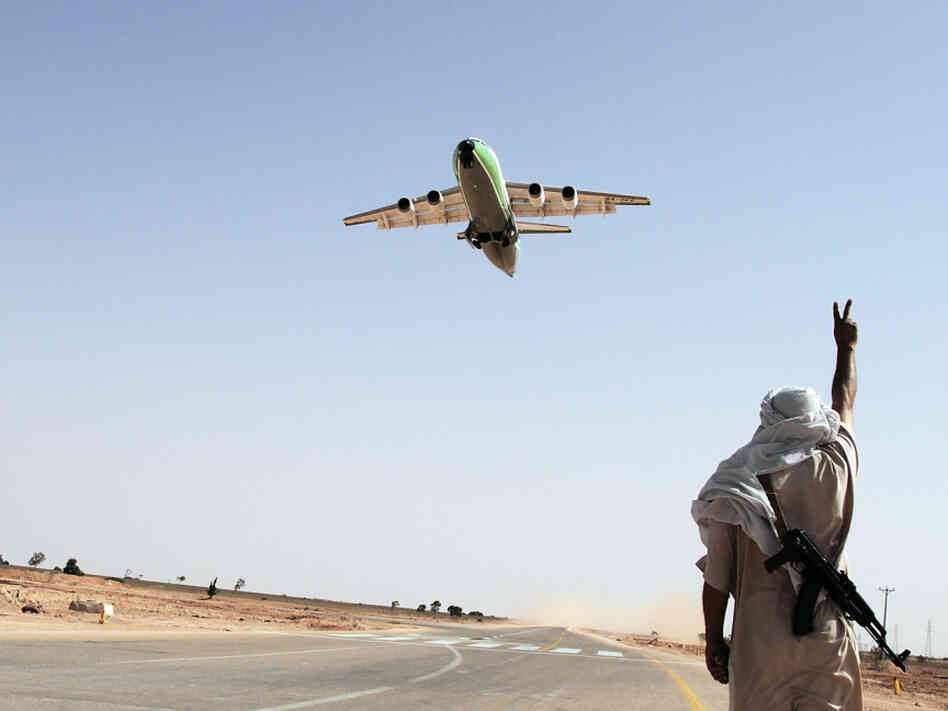 A Libyan rebel fighter flashes a victory sign as an aircraft carrying supplies for the rebels departs along a guarded mile-long stretch of road being used as runway, outside of Rhybat in western Libya, on July 19.